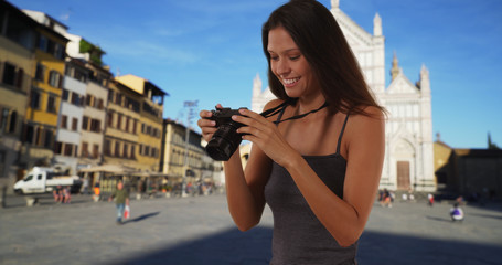 Beautiful tourist woman with dslr camera taking photo in Santa Croce Florence
