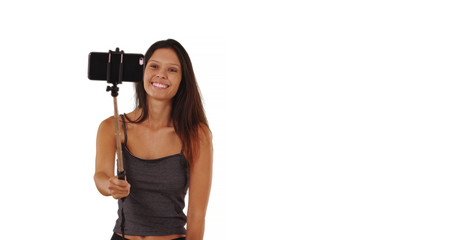 Pretty tourist woman with selfie stick posing for pictures on white background