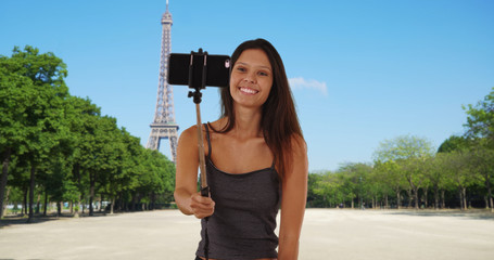 Pretty tourist woman near the Eiffel Tower taking silly photos with selfie stick