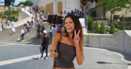 Cute millennial girl vacationing Rome taking silly selfies by the Spanish Steps