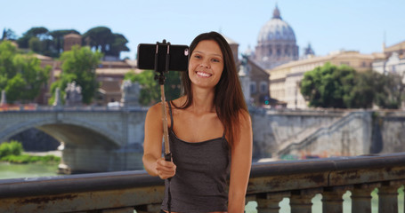 Young tourist woman on bridge in Rome taking selfies near St. Peters Basilica