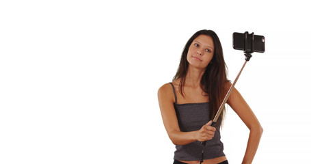 Cute brunette traveler girl using selfie stick in studio with copy space