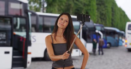 Cute brunette traveler girl on holiday in Europe using selfie stick