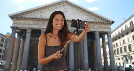 Cute brunette traveler girl in front of the Pantheon in Rome using selfie stick