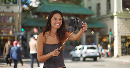 Trendy young tourist woman using selfie stick in Chinatown San Francisco
