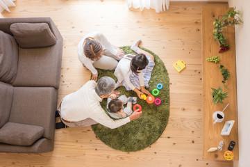 孫のお世話をするシニア夫婦の俯瞰写真