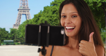 Woman tourist sightseeing in Paris France using selfie stick near Eiffel Tower