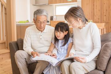 孫娘と絵本を読むシニア夫婦