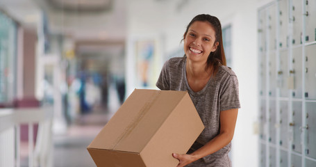 Cheerful young woman at post office holding cardboard package