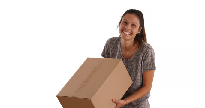 Cheerful young woman carrying cardboard box on white background with copyspace