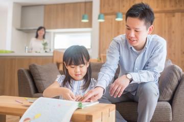 リビングで娘に勉強を教えるお父さん