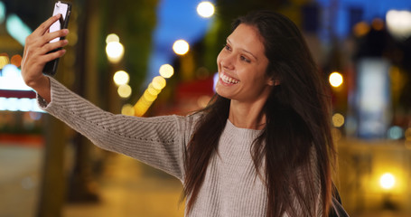Millennial woman on Champs-Elysees taking selfie with mobile phone at night