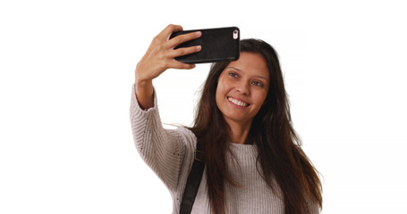 Beautiful female in grey sweater takes phone selfie on white background