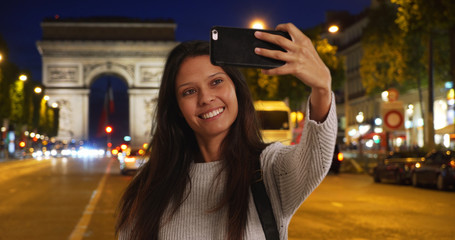 Beautiful female takes phone selfie at night with Arc de Triomphe behind her