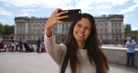Tourist woman sightseeing in England takes phone selfie with landmark behind her