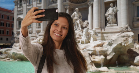 Millennial woman in italy taking phone selfie in front of Trevi Fountain