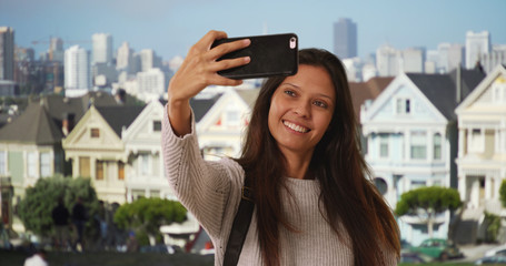 Millennial woman with backpack takes phone selfie in San Francisco neighborhood