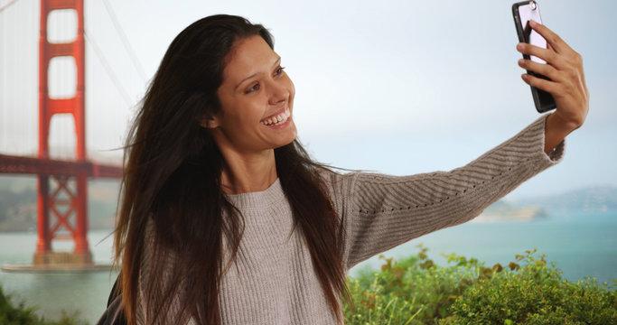 Beautiful female takes selfie near Golden Gate Bridge with mobile phone