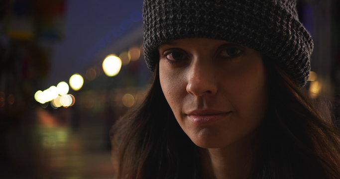 Dramatic close up portrait of millennial woman on boardwalk at night