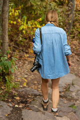photographer walking with digital camera over shoulder on forest path with colorful  fall leaves