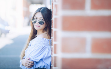 Portrait of young asian woman leaning on the brick wall. Crossed arm and looking at camera.