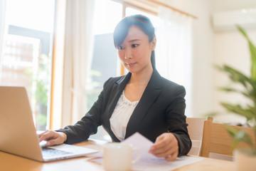 ノートパソコンで仕事をするスーツ姿の女性