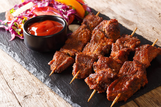 Recipe of a spicy African suya kebab on skewers with fresh vegetable salad and ketchup close-up. horizontal