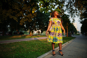 Cute small height african american girl with dreadlocks, wear at coloured yellow dress, posed at sunset.
