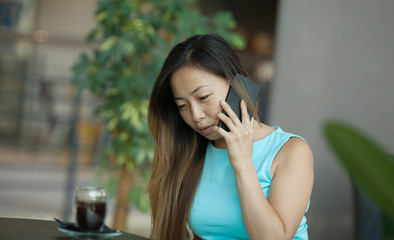 Beautiful Asian lady talking on the phone in cafe.