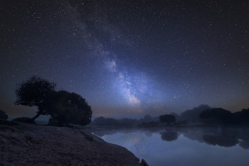 Vibrant Milky Way composite image over landscape of misty lake in Summer