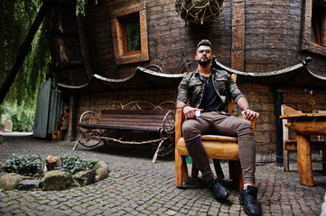 Awesome beautiful tall ararbian beard macho man in glasses and military jacket posed outdoor, sitting on chair against wooden house.