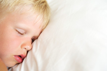 Blondy little boy sleeping on white pillow. Sweet dream concept. Top view.