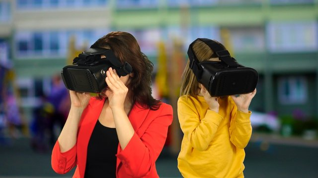 Fashionable, trendy mother and daughter are looking into virtual reality glasses.