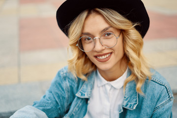 Portrait of cheerful white woman in glasses wearing  hat