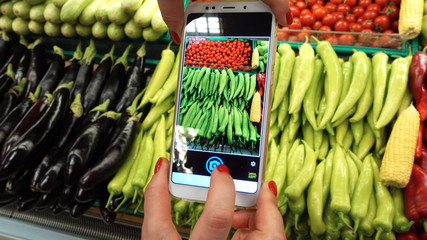 Woman's Hand taking picture of tomatoes and other vegetables using smart phone at grocery store.