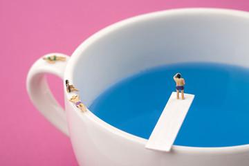 miniature people in mug cup swimming pool