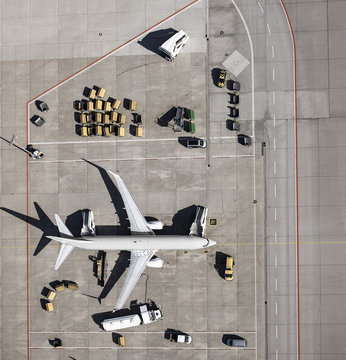 View from above commercial airplane being serviced, prepared on tarmac at airport
