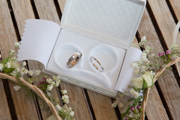 two wedding rings in white case in wooden background with flowers marriage