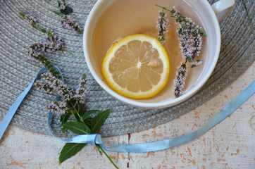 herbal tea with lemon and mint in a white mug