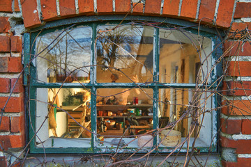 Old leaded painted wood window in an arched red brick wall