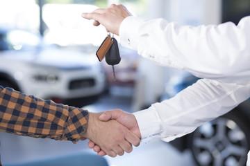 Close-up of two men giving a handshake. Seller holding car keys