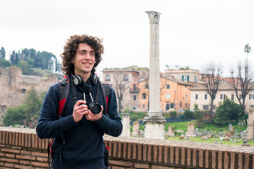 Handsome young tourist with curly hair taking photos of Roman forum in Rome, Italy. Young man travel with his camera