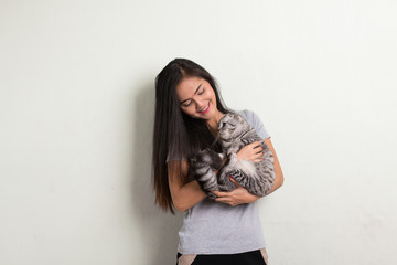 Young happy beautiful Asian woman smiling while holding cute cat