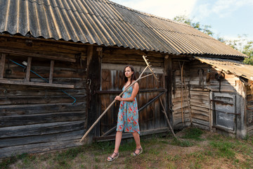 a young woman in a summer retro sarafan dress goes around the yard along the sheds and old rural buildings with rakes on the shoulder