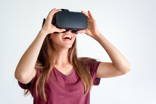 Smiling positive woman wearing virtual reality goggles headset, vr box. Connection, technology, new generation, progress concept. Girl trying to touch objects in virtual reality. Studio shot on gray