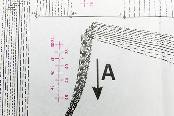 Arrow pointing downward with graphical elements to design clothing.