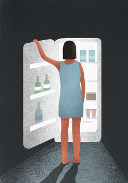 Hungry woman standing at open refrigerator