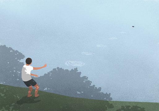 Boy skipping stones at blue lake
