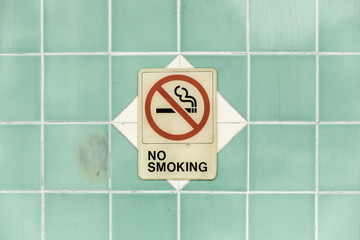 No smoking sign on turquoise tile wall