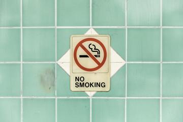 No smoking sign on turquoise tile wall